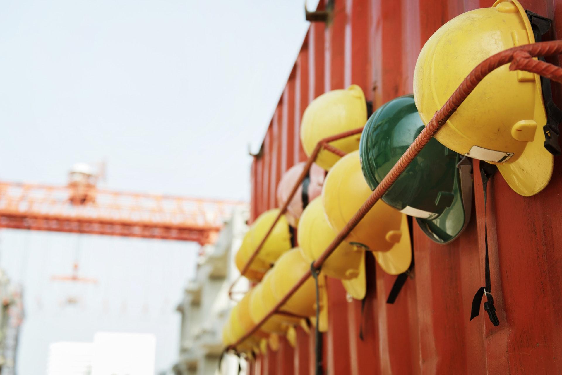 safety first - hängende Bauhelme an einem Container